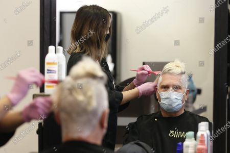 Stock Picture of Steve Severyn gets his hair cut and colored by stylist Colleen Morrow at the Willo Aveda Salon in Roseville, Calif., . The salon closed back in March, due to the coronavirus pandemic, reopened for businesses Friday. New guidelines, are being followed including requiring six feet between patrons, sanitizing each station after every client and providing masks for workers and customers who need them