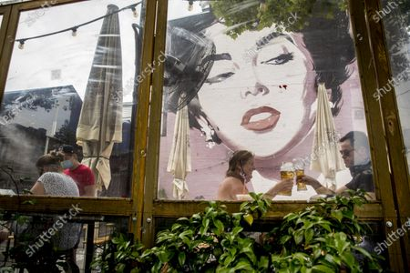Large Elizabeth Taylor mural is visible behind Amber Kirtley, second from right, and Jeff Gullo, right, as they toast with their beers at Dacha Beer Garden in the Shaw neighborhood in Washington, after the District of Columbia gradually loosens stay-at-home rules that have been in place since March 25 because of the pandemic and allows restaurants to resume outdoor dining