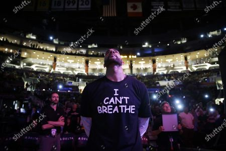 """Los Angeles Lakers' Carlos Boozer, wearing a T-shirt reading """"""""I Can't Breathe"""" stands before team introductions for an NBA basketball game against the Sacramento Kings in Los Angeles. Eric Garner uttered those words six years ago, locked in a police chokehold. It became a rallying cry after his death for demonstrators across the country who protested the killings of African Americans by police. Until this week. George Floyd uttered the exact same words, while handcuffed and pinned at the neck under the knee of a white police officer, galvanizing the movement anew and prompting mass protests around the country"""