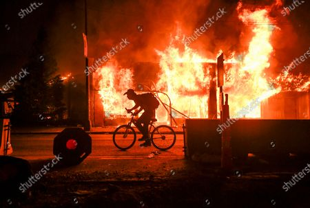 A biker rides past a store set ablaze in response to the death of George Floyd in Minneapolis, Minnesota, USA, 29 May 2020. Floyd's life was cut short after a Minneapolis police officer pinned Floyd's neck to the street for several minutes earlier in the week. Hennepin County Attorney Mike Freeman announced murder and manslaughter charges against the Minneapolis police officer who killed George Floyd Friday afternoon.