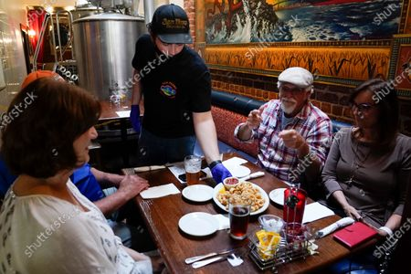 Stock Picture of Tim Stevenson serves an appetizer to customers at San Pedro Brewing Company, in the San Pedro area of Los Angeles