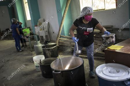 Clara Mocca serves up a pot of beans and rice for 30 U.S. cents at a soup kitchen organized by neighbors in the Villa Maria de Triunfo neighborhood, amid the new coronavirus pandemic, on the outskirts of Lima, Peru