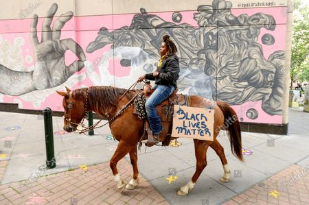 Brianna Nobel rides her horse Dapper Dan through downtown Oakland, Calif., to protest the Memorial Day death of George Floyd who died while in police custody in Minneapolis