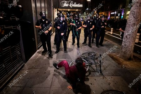 A woman falls off her bicycle as police officers prevent protesters from entering a street during protests over the Minnesota arrest of George Floyd, who later died in police custody, in Los Angeles, California, USA, 29 May 2020. A bystander's video posted online on 25 May, appeared to show George Floyd, 46, pleading with arresting officers that he couldn't breathe as an officer knelt on his neck. The unarmed black man later died in police custody. On 29 May, Hennepin County Attorney Mike Freeman announced third degree murder charges against the Minneapolis police officer who killed George Floyd.