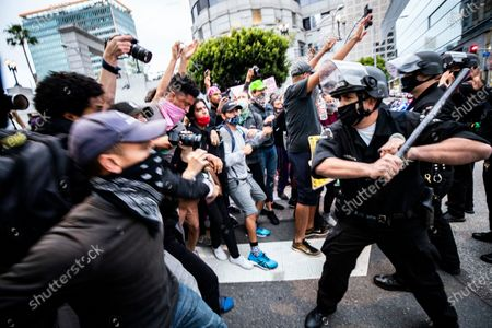 A police officer reacts as protesters try to break through a police blockade during protests over the Minnesota arrest of George Floyd, who later died in police custody, in Los Angeles, California, USA, 29 May 2020. A bystander's video posted online on 25 May, appeared to show George Floyd, 46, pleading with arresting officers that he couldn't breathe as an officer knelt on his neck. The unarmed black man later died in police custody. On 29 May, Hennepin County Attorney Mike Freeman announced third degree murder charges against the Minneapolis police officer who killed George Floyd.