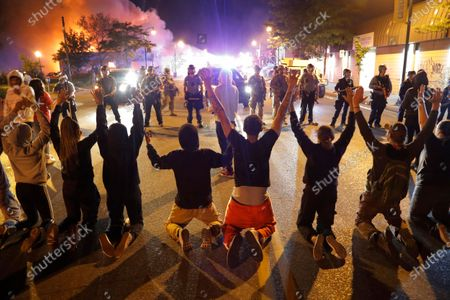 Demonstrators kneel before police, in Minneapolis. Protests continued following the death of George Floyd, who died after being restrained by Minneapolis police officers on Memorial Day