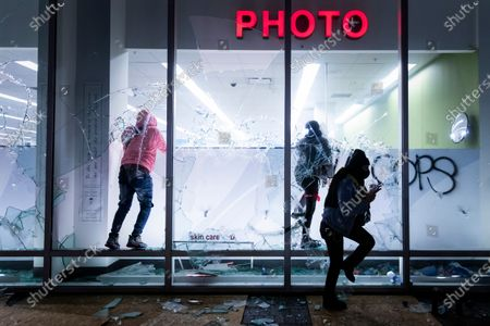 People vandalize a Walgreens store during protests against the Minneapolis police shooting of George Floyd in Oakland, Calif. Floyd died in police custody Monday in Minneapolis