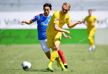 Lee Jae-Sung (L) of Kiel in action against Amos Pieper (R) of Bielefeld during the German Bundesliga second division soccer match between Holstein Kiel and Arminia Bielefeld at Holstein-Stadion in Kiel, Germany, 30 May 2020.