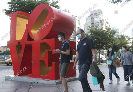 People wear face masks to protect against the spread of the coronavirus as they walk past the Love Sculpture, inspired by the iconic design by American artist Robert Indiana, in Taipei, Taiwan