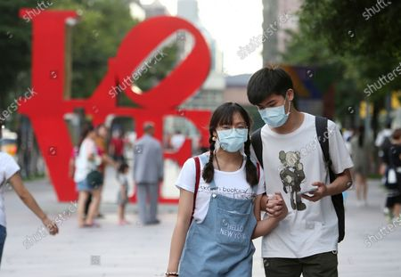 Couple wear face masks to protect against the spread of the coronavirus as the pass in front of the Love Sculpture, inspired by the iconic design by American artist Robert Indiana in Taipei, Taiwan