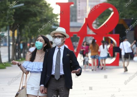 People wear face masks to protect against the spread of the coronavirus as they pass in front of the Love Sculpture, inspired by the iconic design by American artist Robert Indiana in Taipei, Taiwan