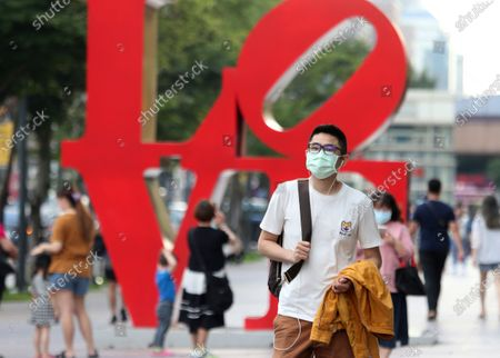 Man wears face mask to protect against the spread of the coronavirus as he passes in front of the Love Sculpture, inspired by the iconic design by American artist Robert Indiana in Taipei, Taiwan