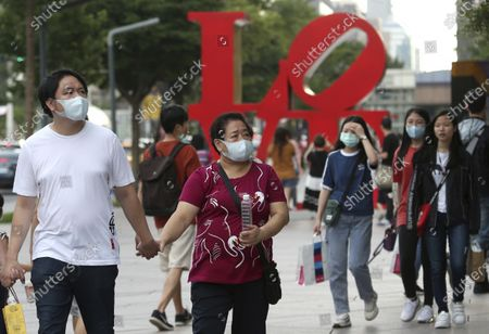 People wear face masks to protect against the spread of the coronavirus as they p[ass in front of the Love Sculpture, inspired by the iconic design by American artist Robert Indiana in Taipei, Taiwan