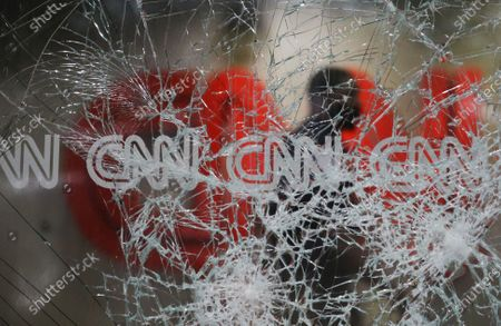 Security guard walks behind shattered glass at the CNN building at the CNN Center in the aftermath of a demonstration against police violence, in Atlanta