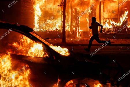 Protestor runs past burning cars and buildings on Chicago Avenue, in St. Paul, Minn. Protests continued following the death of George Floyd, who died after being restrained by Minneapolis police officers on Memorial Day