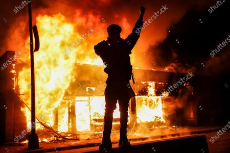 Demonstrator stands beside a fire of a building that was once a check cashing business, in St. Paul, Minn. Protests continued following the death of George Floyd, who died after being restrained by Minneapolis police officers on Memorial Day
