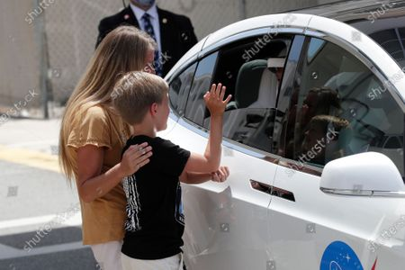 Stock Image of Jack Hurley, 10, waves at his dad NASA astronaut Douglas Hurley, as his wife Karen Nyberg looks on. Hurley and astronaut Robert Behnken walked out of the Neil A. Armstrong Operations and Checkout Building on their way to Pad 39-A, at the Kennedy Space Center in Cape Canaveral, Fla., . The two astronauts will fly on a SpaceX test flight to the International Space Station. For the first time in nearly a decade, astronauts will blast into orbit aboard an American rocket from American soil, a first for a private company
