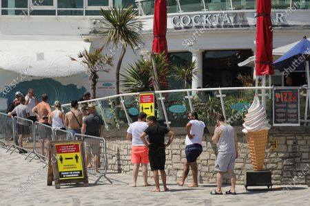 "Photo taken on May 30, 2020 shows people queuing at a bar on Bournemouth Beach in Bournemouth, Britain. British Prime Minister Boris Johnson on Thursday unveiled some ""limited"" and ""cautious"" easing of the country's coronavirus lockdown measures."