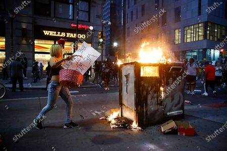 Protester throws items in to a fire, during a demonstration in Philadelphia, over the death of George Floyd, a black man who was in police custody in Minneapolis. Floyd died after being restrained by Minneapolis police on Memorial Day