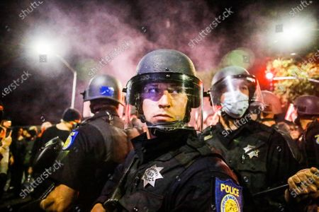 A group of policemen stand, surrounded by protesters during the demonstration.A peaceful protest, spurred by the death of George Floyd, turned violent as protesters clashed with police, throwing rocks and bottles at police while police responded by shooting pepper spray balls at protesters and using flash bang grenades to disperse the crowd.