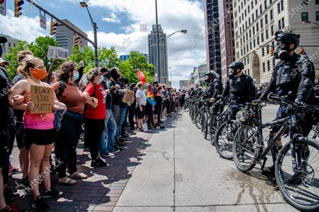 Police officers form a wall in front of protestors as they gather at the Ohio Statehouse during a protest in solidarity with the recent death of George Floyd on May 30th, 2020 in Columbus, OH.