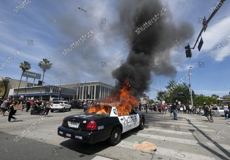 Police vehicle is burning during a protest over the death of George Floyd, a handcuffed black man in police custody in Minneapolis, in Los Angeles