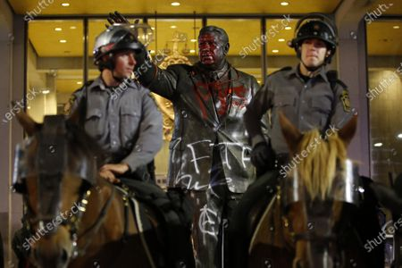 Vandalized statue of the late Philadelphia Mayor Frank Rizzo, who also served as the city's police commissioner, stands behind mounted State Police officers outside the Municipal Services Building in Philadelphia, The statue was vandalized during a protest over the death of George Floyd, a black man who died in Minneapolis police custody on May 25