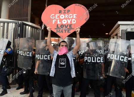 A Protestor is seen holding up a sign stating George Floyd Love Over Hate as Miami Police in Riot gear stand behind him during the protests for George Floyd, Miami, Florida, USA - 30 May 2020