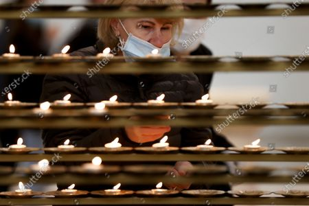 A woman wearing face mask lights a candle during the Sunday Mass at the Mother Teresa cathedral amid the ongoing coronavirus COVID-19 pandemic in Pristina, Kosovo, 31 May 2020. Faithful attended the Sunday mass for the first time since mid-March when the Kosovo's government closed borders and suspended activities in a bid to control the spread of the COVID-19 disease caused by the SARS-CoV-2 coronavirus in the West Balkan country.