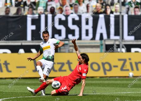 Stock Photo of Moenchengladbach's Stefan Lainer, left, duels for the ball with Union's Neven Subotic during the German Bundesliga soccer match between Borussia Moenchengladbach and Union Berlin in Moenchengladbach, Germany, . The German Bundesliga becomes the world's first major soccer league to resume after a two-month suspension because of the coronavirus pandemic