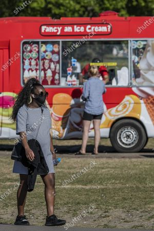 Getting an ice cream from the Mr Whippy van in Brockwell park - People enjoy the sun on Clapham Common after the Government eased restrictions and allowed people to meet. The eased 'lockdown' continues for the Coronavirus (Covid 19) outbreak in London.