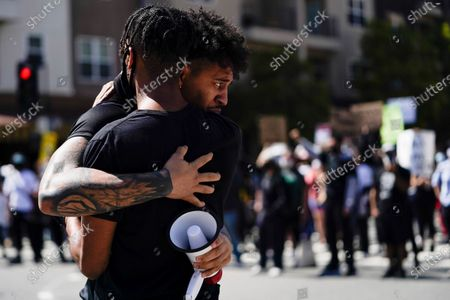 Demonstrators embrace outside the Long Beach Police Department, in Long Beach during a protest over the death of George Floyd. Floyd died May 25 after he was pinned at the neck by a Minneapolis police officer