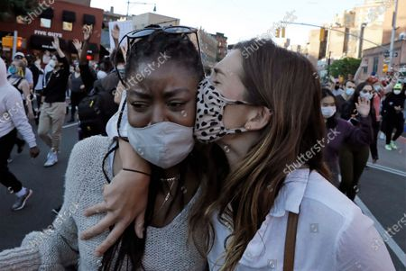 Two women embrace during a demonstration over the death of George Floyd, who died in police custody in Greenwich Village, New York, USA, 31 May 2020. A bystander's video posted online on 25 May, shows George Floyd pleading with arresting officers that he couldn't breathe as an officer knelt on his neck. The unarmed black man soon became unresponsive, and was later pronounced dead. According to reports on 29 May, Derek Chauvin, the police officer at the center of the incident, has been taken into custody and charged with murder in the death of George Floyd.
