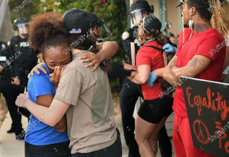 Protestors embrace as another is led away in handcuffs on 5th St. in Santa Monica Sunday. (Wally Skalij/Los Angeles Times)