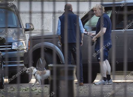 Stock Image of Prime Minister Boris Johnson holds a tennis racket as he arrives back in Downing Street with his dog Dilyn after going out for exercise. The government have announced new measures from Monday to allow groups of six people to meet outdoors.