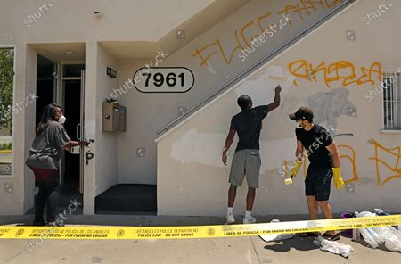 D'Angela Proctor, left, with her son Nikolas Steed, center, get a helping hand from neighbor Chris Hendrickson, right, while covering up graffiti on the building that houses Wayfarer, a social impact production company that Proctor heads as the CEO, on 3rd Street in the Fairfax District on Sunday, May 31, 2020. (Christina House / Los Angeles Times)