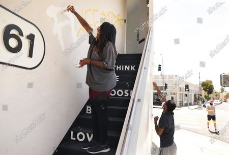 D'Angela Proctor, left, with her son Nikolas Steed, right, cover up graffiti on the building that houses Wayfarer, a social impact production company that Proctor heads as the CEO, on 3rd Street in the Fairfax District on Sunday, May 31, 2020. (Christina House / Los Angeles Times)