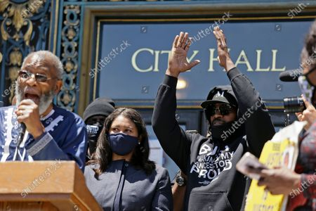 "Stock Picture of Jamie Fox applauds while standing with Mayor London Breed as they listen to Rev. Amos Brown, left, speak during a ""kneel-in"" to protest police racism on the steps of City Hall, in San Francisco"