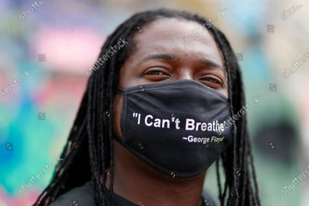 """Wearing a mask he designed himself that reads, """"I can't breathe"""", artist Theo Ponchaveli poses in front of mural he painted in Dallas, depicting the scene of George Floyd in custody. Floyd is a black man who died in police custody on Memorial Day in Minneapolis, sparking national protests"""