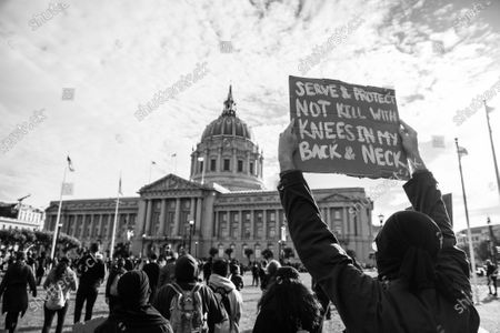 A sign is held up during a demonstration at City Hall in San Francisco, California after the death of George Floyd.