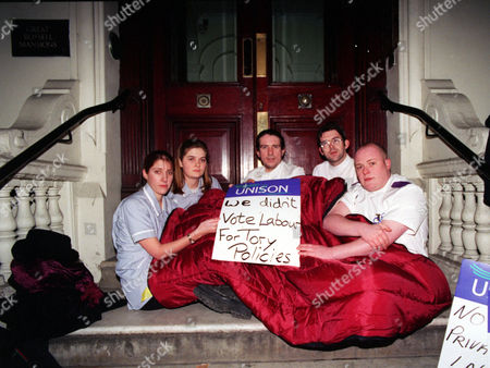 Stock Photo of Nurses Keep Warm Under A Duvet On The Steps Of Health Minister Frank Dobsons Home. From Left To Right; Kate Playle (19) Becky Regan (20) John Quinn (36) Noel Moone (28) And Jon Dempsey (23). The Student Nurses Fear They Will Be Made Homeless By Nhs Privatisation And Due To A Hospital Merger It Means That Staff Residences Will Be Cut And That Staff Jobs Will Be Privatised.