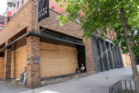 Stock Image of Looting and destruction follow peaceful protests at Sunday night in SoHo area of Manhattan. View of Eileen Fisher store with people enjoying day on stoop of the store
