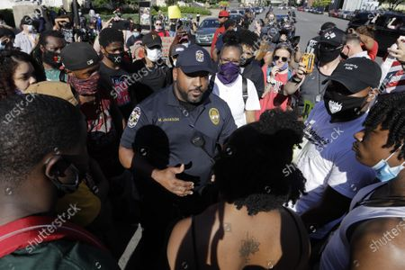 Louisville Metro Police Department officer Michael Jackson talks with a protester, in Louisville, Ky. The protest was over the deaths of George Floyd and Breonna Taylor. Taylor, a black woman, was fatally shot by police in her home in March and Floyd, a black man, died after being restrained by Minneapolis police officers on May 25. (AP Photo/Darron Cummings