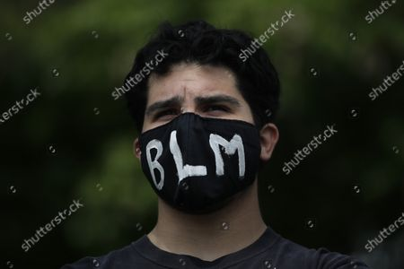 """Demonstrator wears a mask with """"BLM"""" written on it, the letters referring to """"Black Lives Matter,"""" during a protest over the death of George Floyd, in Anaheim, Calif. Floyd died after being restrained by Minneapolis police officers on May 25"""