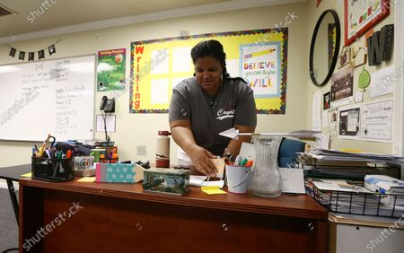 Ka Washington, special education staff member at Desert Heights Preparatory Academy, arranges her desk in her classroom, in Phoenix, returning to her classroom for only the second time since the coronavirus outbreak closed schools. Arizona Superintendent of Public Instruction Kathy Hoffman released guidelines on Monday for reopening the state's K-12 schools in August