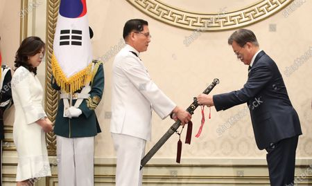President Moon Jae-in (R) ties a tassel onto the sword of Kim Jung-soo, new Vice Chief of Naval Operations, during a ceremony at the presidential office Cheong Wa Dae in Seoul on 02 June 2020, to mark Kim's inauguration. The traditional Korean sword, Sam Jeong Geom, or the Three Spirits Sword, bears President Moon Jae-in's name in Korean and represents the three spirits of defense of the country, unification and prosperity, as well as the Army, Navy and Air Force.