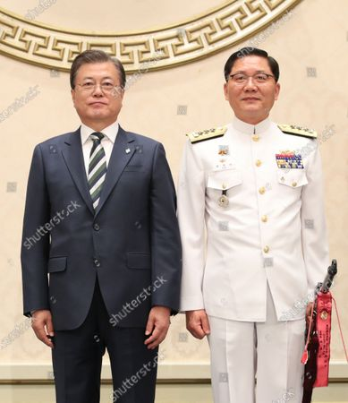 President Moon Jae-in (L) poses for a photo with Kim Jung-soo, new Vice Chief of Naval Operations, after tying a tassel to Kim's sword during a ceremony at the presidential office Cheong Wa Dae in Seoul, South Korea, on 02 June 2020, to mark Kim's inauguration. The traditional Korean sword, Sam Jeong Geom, or the Three Spirits Sword, bears President Moon Jae-in's name in Korean and represents the three spirits of defense of the country, unification and prosperity, as well as the Army, Navy and Air Force.