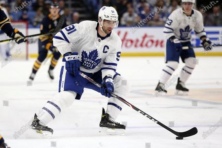 Toronto Maple Leafs forward John Tavares (91) carries the puck during the first period of an NHL hockey game against the Buffalo Sabres in Buffalo, N.Y. Among the unknowns about the NHL returning amid the coronavirus pandemic is what the on-ice product might look like