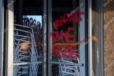 "Spray paint the reads ""Racists Dine Here"" is seen on a revolving door or a restaurant near the White House in Washington, after a boring of protests over the death of George Floyd. Floyd died after being restrained by Minneapolis police officers"