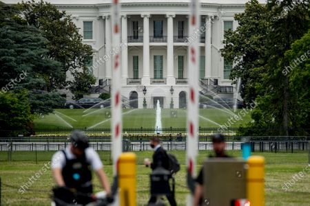 The White House is visible as uniformed Secret Service agents stand at a checkpoint on Constitution Avenue in the morning hours in Washington, as protests continue over the death of George Floyd. Floyd died after being restrained by Minneapolis police officers
